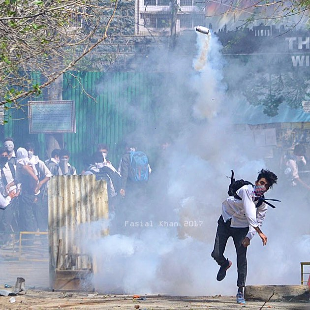 A student returns the teargas canister fired by Indian police during clashes in Srinagar ,Kashmir on April 17, 2017.